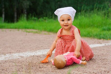 Small pretty girl playing with a doll in the park Stock Photo - 3496936