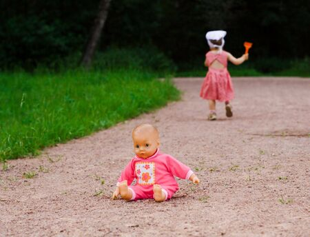 Pink doll left by small girl on the road photo