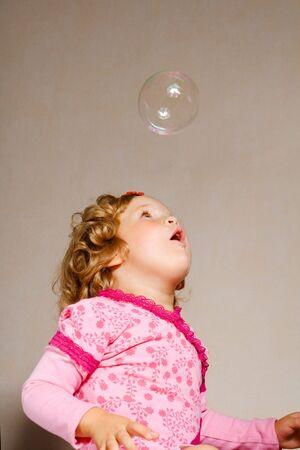 Small pretty girl with soap bubble photo