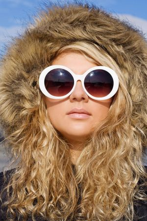 Beautiful girl with curly hair in white sun glasses