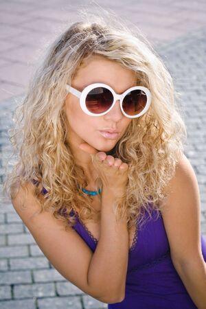 Beautiful blonde girl in white sun glasses