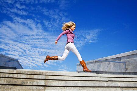 Beautiful girl running against blue sky photo