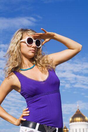 Girl in white sun glasses against blue sky photo