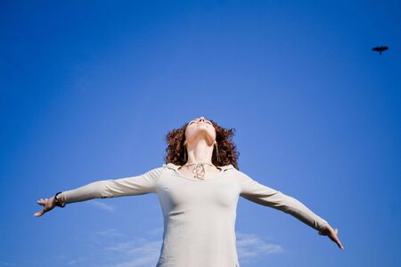 Young woman agains blue sky with arms outstreched photo