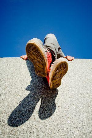 Girl legs in red sneakers against blue sky