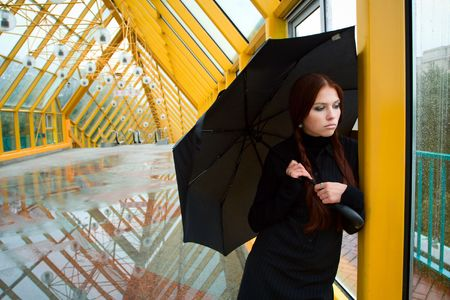 Pretty sad girl with umbrella by the window