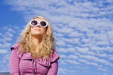 Beautiful girl in big sun glasses against blue sky photo