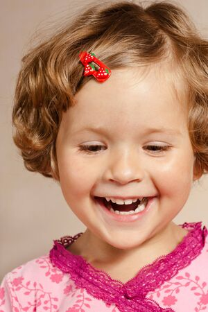 Smiling pretty young girl with a red hair-pin