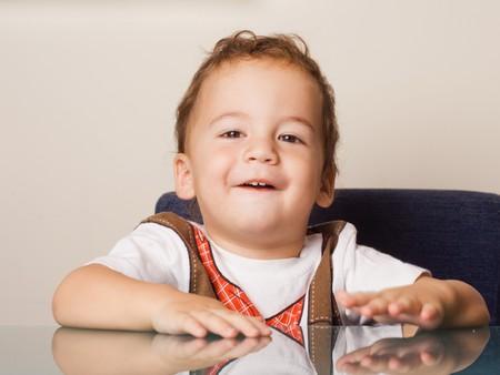 Niño sentado en una mesa de vidrio Foto de archivo - 4117540