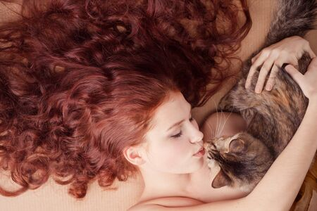 Young beautiful girl tying on the floor with a cat Stock Photo