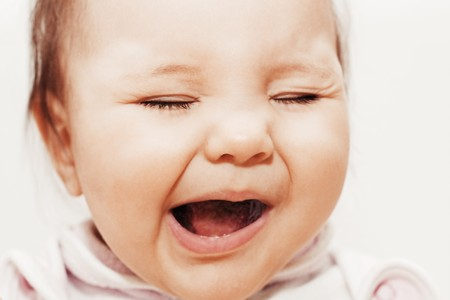 Small pretty crying baby on white background photo