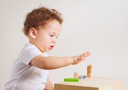 Small boy playing with colorful toys on white background