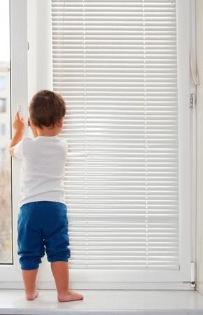 windowsill: Small boy standing on white window-sill