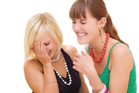 Two young pretty girls laughing on white background