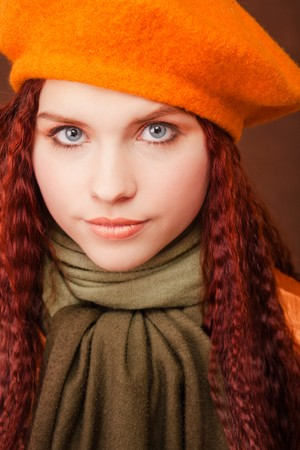 Young beautiful girl in orange beret on dark background photo