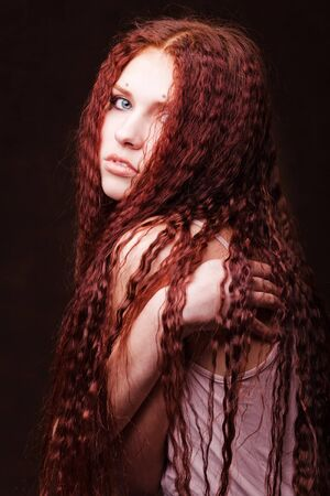 strand of hair: Young beautiful girl woth long red hair