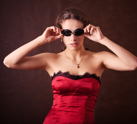 Pretty young girl in red dress and swinmming glasses