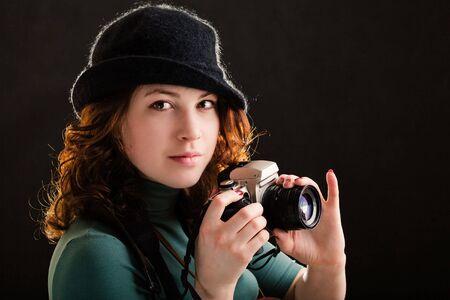 Girl holding a photo on black background photo