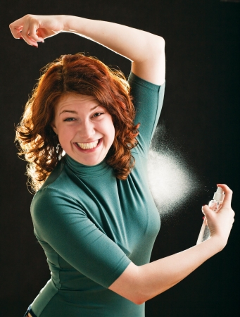 Happy young girl with deodorant on white background