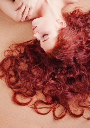red head: Young beautiful girl with long hair lying on the floor Stock Photo
