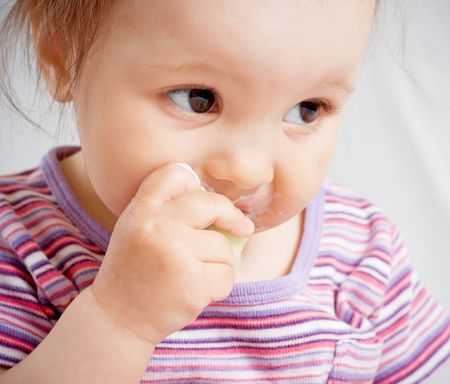 Small girl biting a piece of food photo