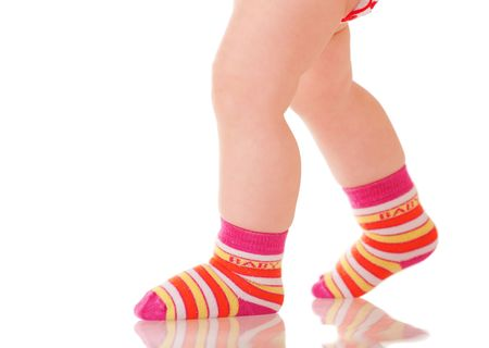 the first step: Baby legs in colorful socks walking on glass surface Stock Photo