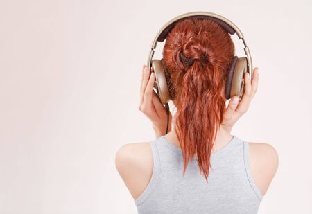 Girl with red hair wearing big headphones