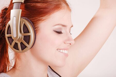 Young pretty smiling girl in big headphones photo