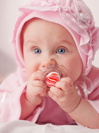 small cute baby holding a red dummy stock photo picture and royalty