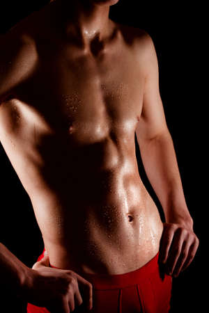 muscled: Young man muscled body on dark background Stock Photo