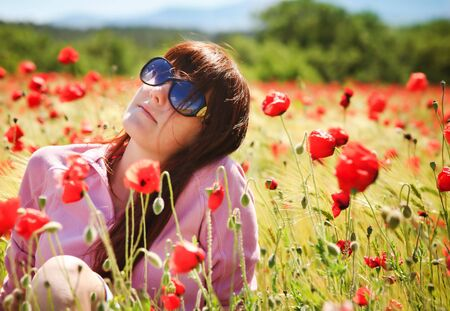 sunburnt: Pretty young girl in sunglasses with red flowers Stock Photo