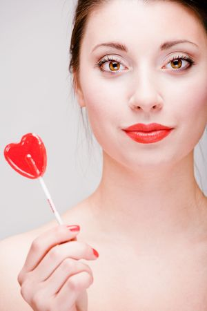 Young pretty girl holding a lollipop photo
