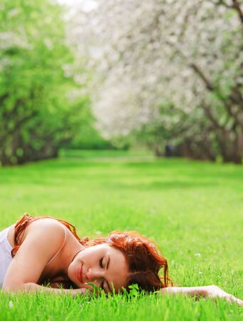 Young pretty girl sleeping in grass Stock Photo