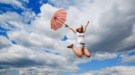 woman sandals: Young girl jumping with an umbrella Stock Photo