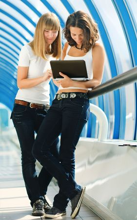 Two young pretty girls with a computer photo