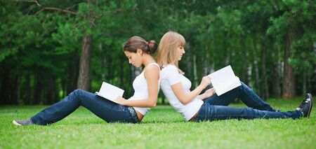 Two young girls sitting on the grass photo