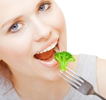 Young girl eating broccoli on white background