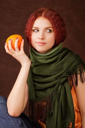 Young pretty girl holding an orange photo