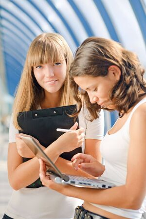 Two young pretty girl with a laptop photo