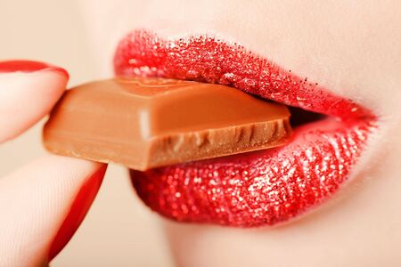 finger to lips: Red lips eating chocolate close-up shot