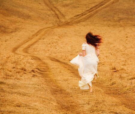 Girl in white dress is running on the road