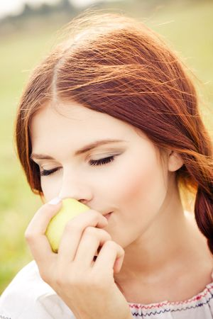 Young pretty girl eating an apple Stock Photo