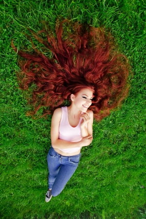 Girl with red hair lying on green grass