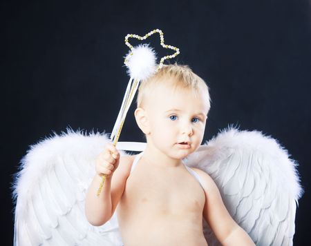 Small child in angel wings on black background photo
