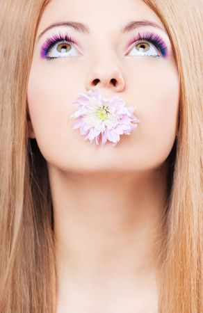 Pretty young girl with a flower in mouth portrait photo
