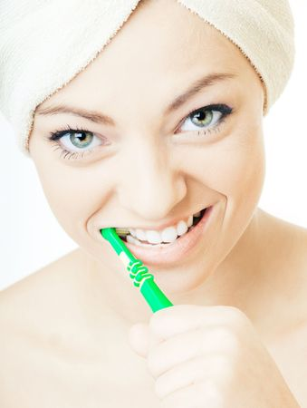 Young pretty girl cleaning teeth with a toothbrush photo