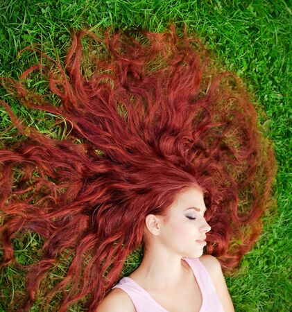 Young pretty girl with red hair lying on grass