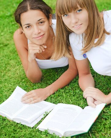 Two young girls on green grass photo