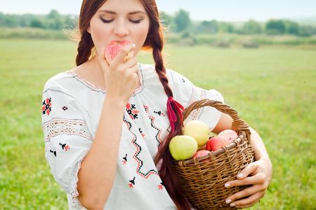 Young girl holding a basket with apples