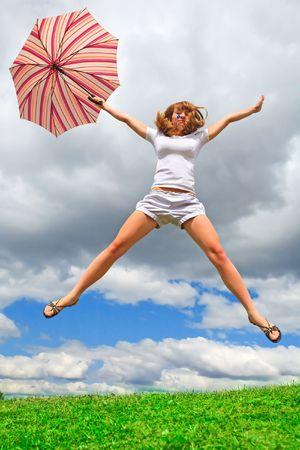 beine spreizen: Young Girl jumping mit einem Regenschirm